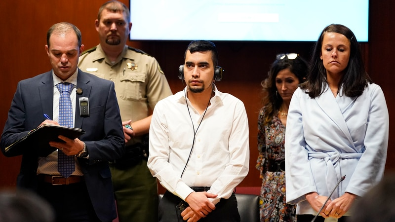 Cristhian Bahena Rivera, center, stands with his attorney Jennifer Frese, right, as he listens...