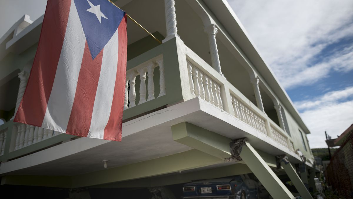 A Puerto Rican flag hangs from the porch of a home that collapsed on top of parked cars after an earthquake hit Guanica, Puerto Rico, Monday, Jan. 6, 2020. A 5.8-magnitude quake hit Puerto Rico before dawn Monday, unleashing small landslides, causing power outages and severely cracking some homes. There were no immediate reports of casualties. (AP Photo/Carlos Giusti)