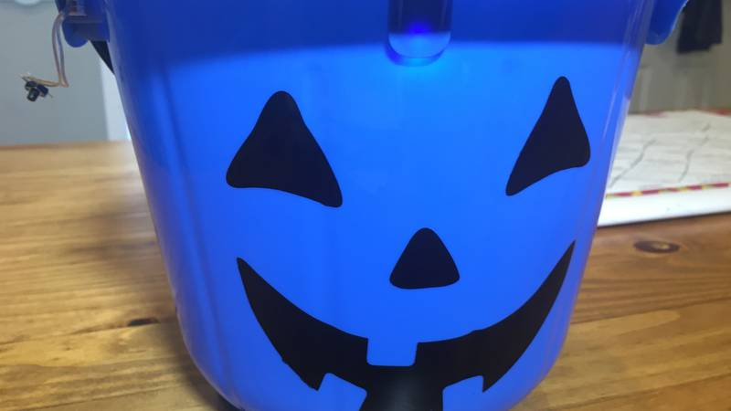 Children with autism carry blue buckets or jack-o-lanterns during Halloween to raise awareness.