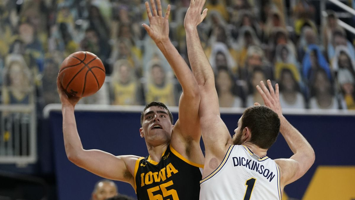 Iowa center Luka Garza (55) is defended by Michigan center Hunter Dickinson (1) during the...
