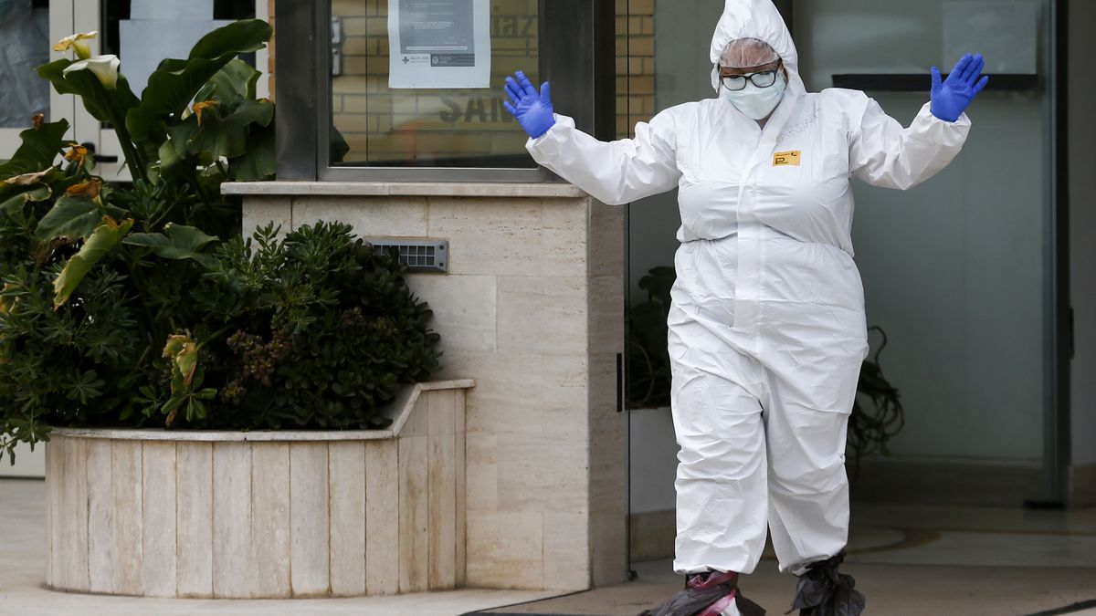 A medical staffer gestures after performing swabs for coronavirus in the Santa Cecilia nursing home in Civitavecchia, near Rome, Saturday, April 17, 2020. A scandal over coronavirus infections and deaths in Italy's nursing homes took on broader dimensions Friday, with the National Institutes of Health conservatively estimating that at least 6,773 residents had died since Feb. 1, 40% of them either infected with the virus or with COVID-19 symptoms. (Cecilia Fabiano/LaPresse via AP)