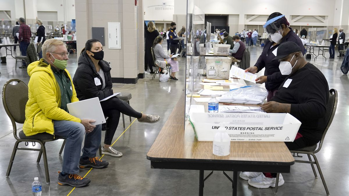 Election workers, right, verify ballots as recount observers, left, watch during a Milwaukee...