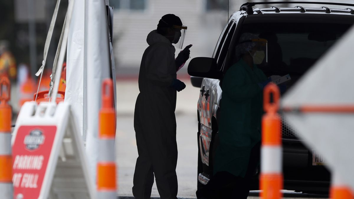 FILE - A medical staff administer COVID-19 tests to the public in the Iowa Events Center parking lot, Tuesday, April 28, 2020, in Des Moines, Iowa. (AP Photo/Charlie Neibergall)