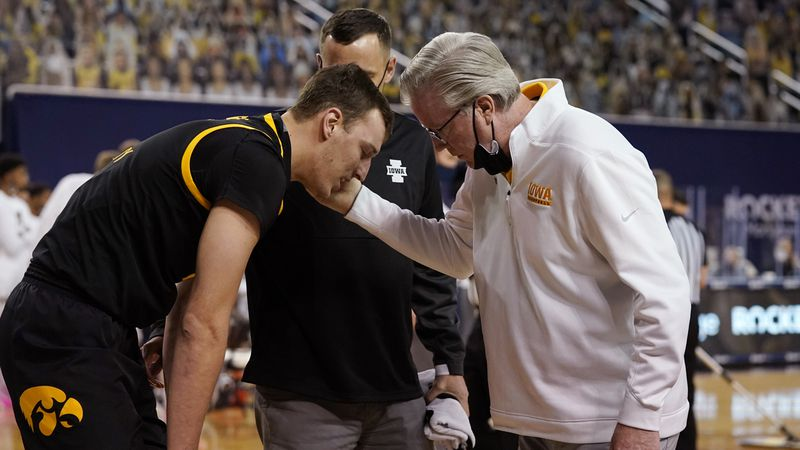 Iowa forward Jack Nunge (2) is checked by head coach Fran McCaffery during the first half of an...