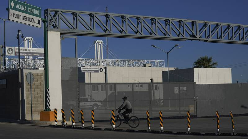 A man rides his bike past the closed main entrance of the international border bridge that...