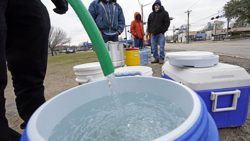 FILE - In this Feb. 18, 2021, file photo, a water bucket is filled as others wait in near...