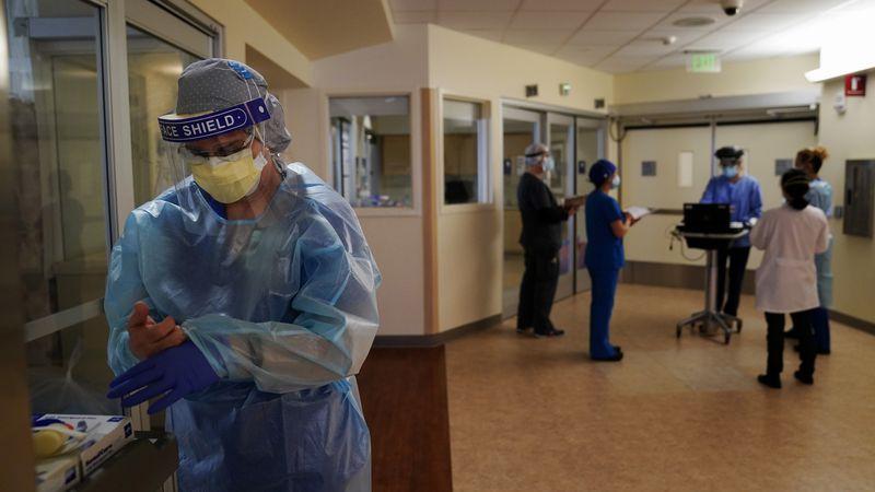 FILE - In this Jan. 7, 2021 file photo, registered nurse Merri Lynn Anderson puts on her...