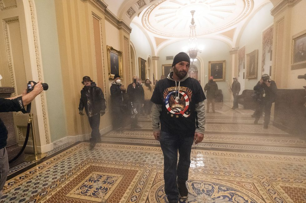 Smoke fills the walkway outside the Senate Chamber as supporters of President Donald Trump are...