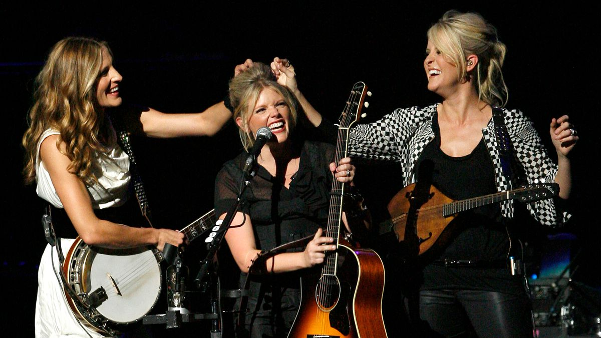 FILE - In this Oct. 18, 2007 file photo, Emily Robison, left, and Martie Maguire, right, adjust Natalie Maines' hair as the Dixie Chicks perform at the new Nokia Theatre in Los Angeles. The Grammy-winning country group have dropped the word dixie from their name and are now going by The Chicks. The move follows a decision by country group Lady Antebellum to change to Lady A after acknowledging the word's association to slavery.