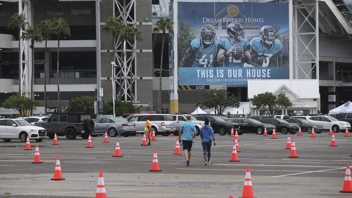 FILE - In this Sept. 13, 2020 file photo, fans walk through a parking lot with cones to social distance the cars before an NFL football game between the Jacksonville Jaguars and the Indianapolis Colts in Jacksonville, Fla.  The Jacksonville Jaguars are the latest NFL team dealing with a positive COVID-19 test. The Jaguars released a statement Saturday, Oct. 17,  saying a practice squad player was confirmed as testing positive for the coronavirus a day earlier.