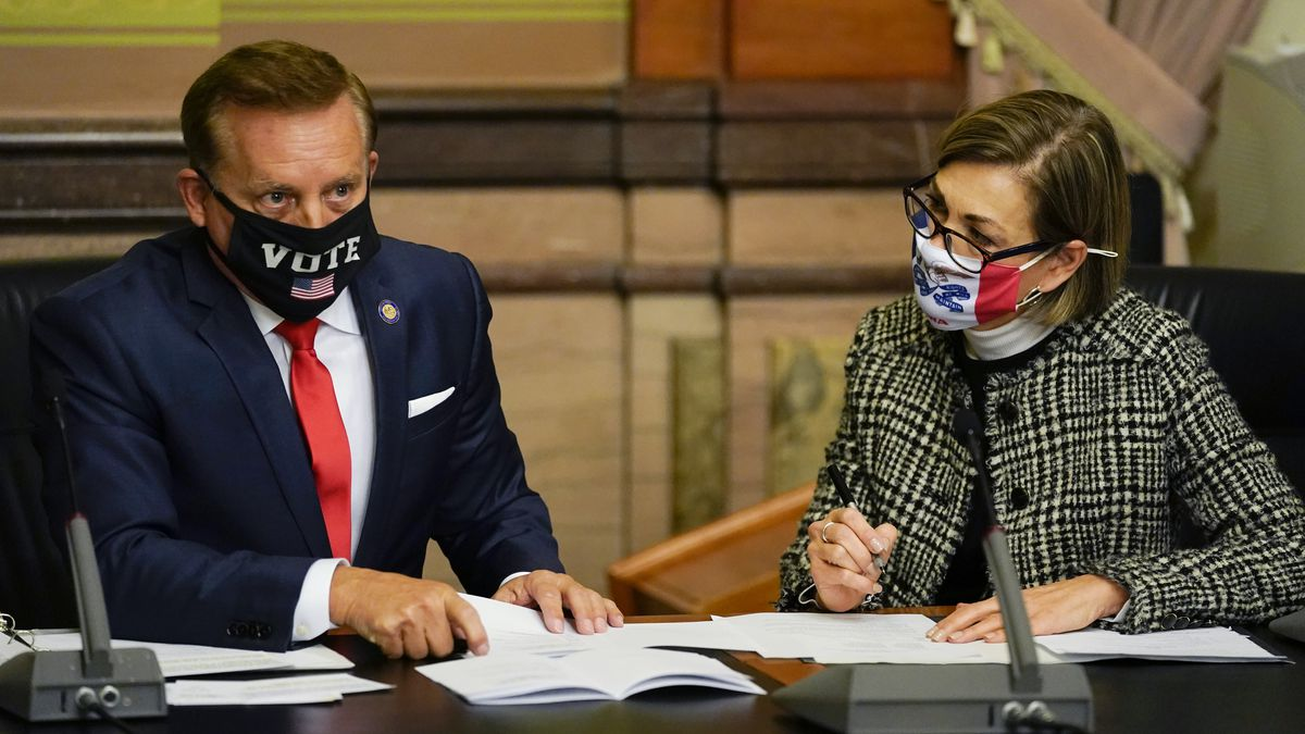 Iowa Secretary of State Paul Pate, left, and Iowa Gov. Kim Reynolds tally the votes cast by...