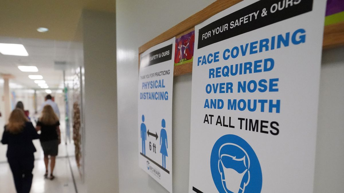 Signs in a hallway reminds students to wear masks and distance themselves at Fox Trail Elementary School, Friday, Oct. 9, 2020, in Davie, Fla. Broward County, Florida schools began a phased reopening for face-to-face eLearning Friday.