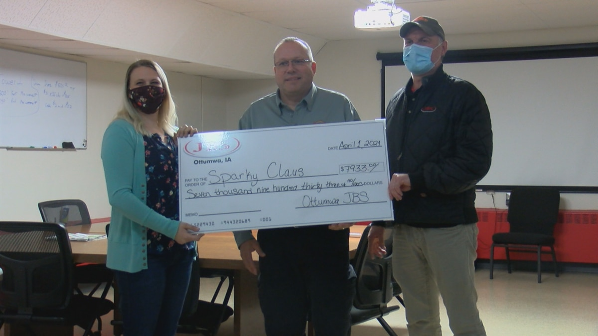 A nearly $8000 check from JBS to Ottumwa Fire's Sparky Claus program